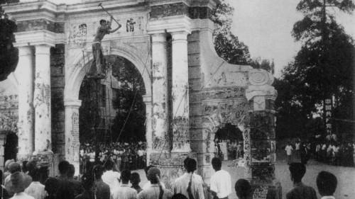 """1966年清华大学校门被拉倒前,红卫兵砸毁牌坊""""清华园""""三个大字。"""