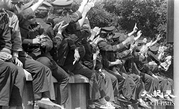 六四期间的北京街头,坐在街边的武警向游行的学生和市民挥手。