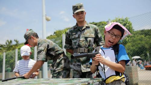 小學生們在士兵的指導下假裝使用手槍作出反應。